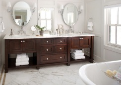 Large master bath has been nicely updated. Marble surfaces, dark furniture grade cabinetry and shiny new fixtures and lighting all add to the luxurious look and feel of this bathroom.