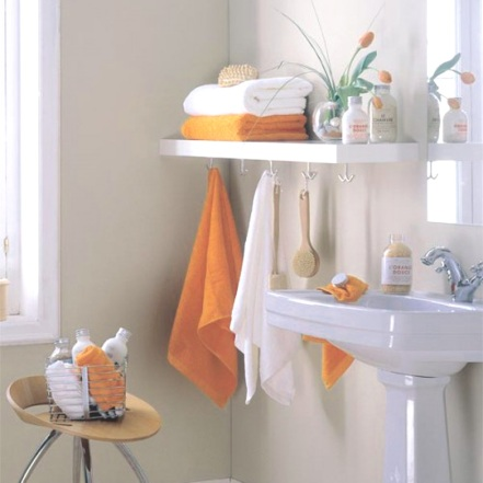 Charming guest bath with pedestal sink and storage idea for this small space. Love the orange!