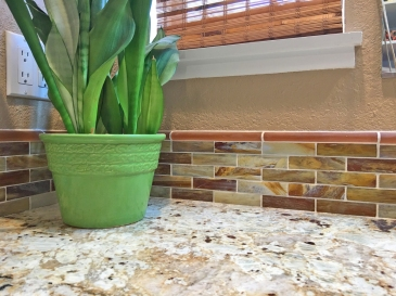 Close up of granite vanity and glass tile backsplash of bathroom remodel.