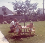 This is me and my little sister and our grandfather at our home in Westminster, enjoying watermelon.